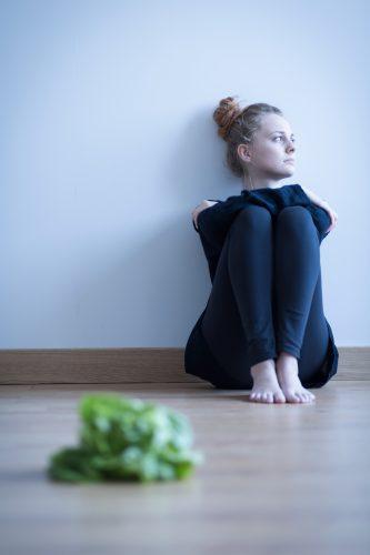 Frau mit Essstörung, sitzt nachdenklich vor Salat